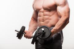 Image of muscle man posing in studio. doing bicep curls - stock photo