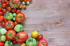 Fresh red and green tomatoes on a table at the left, on the righ Stock Photos