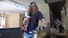 Nanny with baby in hands cooking mix meal in pot and taste. 4K - stock footage