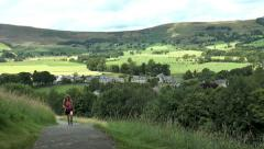 Young woman walking up hill path. Backdrop of scenic Peak District village. Stock Footage