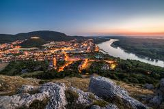 View of Lit Small City with River from the Hill at Sunset Kuvituskuvat