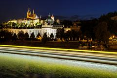 Prague castle in Hradcany with Vlatava river and lights from boats - stock photo