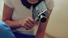 Young woman making movie using retro movie camera Stock Footage