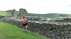 Pretty young woman taking picture over boundary wall of Peveril Castle grounds. Stock Footage