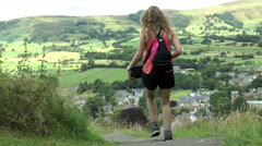 Young woman descending hill path. Backdrop of scenic Peak District village. - stock footage