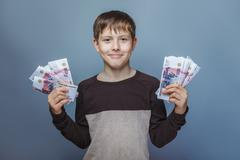 Boy teenager European appearance ten years  holding a wad  of m - stock photo