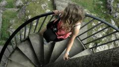 Young woman walking down spiral staircase at Peveril Castle, Peak District. Stock Footage
