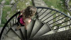 Young woman walking up spiral staircase at Peveril Castle, Peak District. Stock Footage