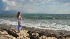 Woman in love standing on stones, stormy sea waves splashing, romantic mood Stock Footage