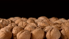 A lot of walnuts, on black, rotation Stock Footage