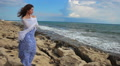 Pretty young woman in romantic mood standing near sea, looking at stormy waves Footage