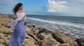 Sad lonely young woman looking at stormy sea, waves splashing, rocky shore, wind Footage