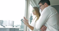Young happy businesspeople with pad by the window Stock Footage
