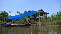 Longtail Boat Moored Along the River in Fishermans Village Stock Footage