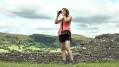 Pretty young woman taking pictures from Peveril Castle grounds, Peak District. Stock Footage