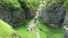 Walkers in Hope Valley alongside Peveril Castle, Peak District. Stock Footage
