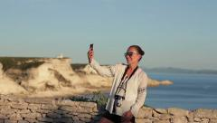 Happy girl on vacations taking self photo on sea background  HD Stock Footage