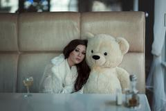 The sad girl sits at a table with toy bear. Stock Photos