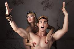 Guy with the crown on head sings his arms. - stock photo