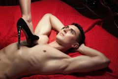 Guy on the chest is female foot in shoe heel. - stock photo