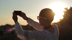 Young woman uses a smartphone to video a beautiful view at sunset HD - stock footage
