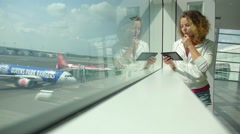 Passenger Traveler Woman in Airport Waiting for Flight and Using Tablet Stock Footage