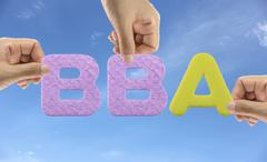 Hand arrange alphabet BBA of acronym Bachelor of Business Administration. Stock Photos