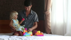 Little blonde daughter plays toy constructor with father Stock Footage