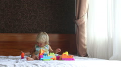 Little blonde girl plays with toy constructor on sofa Stock Footage