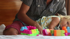 father plays with little daughter composing constructor kisses - stock footage