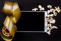 Tablet pc on dark background with attributes of cinema Stock Photos