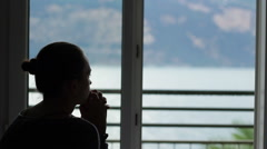 Silhouette of a young sad woman sitting near the window HD Stock Footage