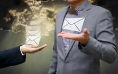 Stock Photo of Businessman get email in hand with shiny sky background