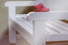 Pink shoes standing on a white bench. Stock Photos