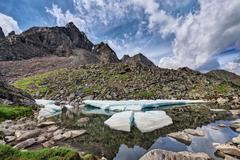 Melting ice floes on a small mountain lake - stock photo
