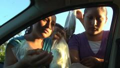 Mexican girls selling fruit through car window Stock Footage