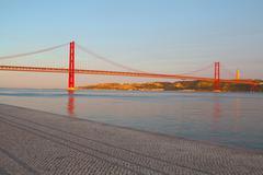 The 25 de Abril Bridge is a suspension bridge on river Tejo, Lisboa. - stock photo