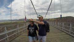 Married couple holding hands walking on Royal Gorge bridge Stock Footage
