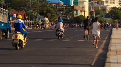 Scooters traffic along resort city street man runs by in morning Arkistovideo