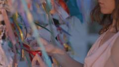Closeup of woman tying a ribbon to the wishing tree. Traditions, symbol of luck Stock Footage