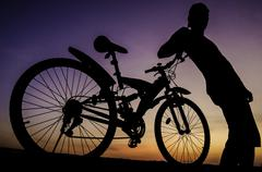 Silhouette of cyclist with twilight sky - stock photo