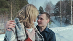 Young couple in love on a winter vacation enjoying the nature and drinking hot Stock Footage