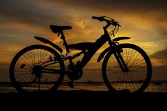Silhouette of mountain bike with sunset sky beside sea Stock Photos