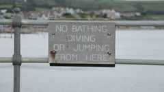 No Diving Sign with person walking by Stock Footage
