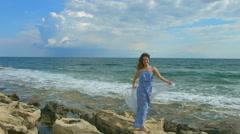 Happy beautiful woman standing on rocky sea beach, foamy waves crashing ashore Stock Footage