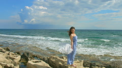 Beautiful brunette woman in maxi dress enjoying windy day on seashore, vacation Stock Footage