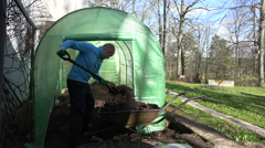 Man shake out compost from wheelbarrow into eco greenhouse. 4K Stock Footage