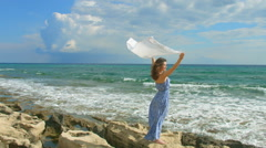 Woman standing on seashore, white scarf waving in the wind. Symbol of freedom Stock Footage