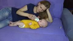 Loving mom give newborn girl bottle of milk. 4K Stock Footage
