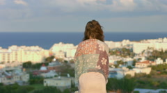 Woman enjoying sea breeze on hill, looking at seaside town. Feeling of freedom Stock Footage